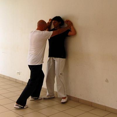 Femme tenue par les poignets contre un mur